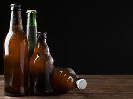 garrafas de cerveja em fundo preto foto