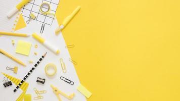 papelaria de escritório plano com espaço de cópia e clipes de papel em fundo amarelo foto
