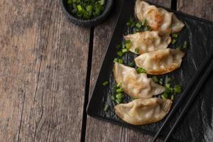 postura plana do prato de bolinho asiático com ervas e espaço de cópia foto