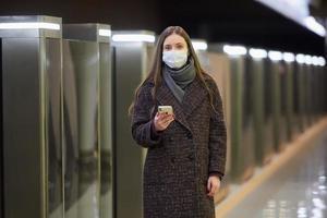 uma mulher com uma máscara facial à espera de um trem e segurando um smartphone foto