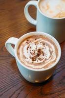 chocolate quente e chocolate em xícara ou caneca branca foto