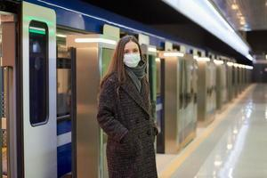 uma garota com máscara cirúrgica está mantendo distância social em uma estação de metrô foto