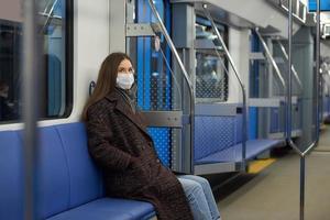 uma mulher com uma máscara médica está mantendo distância social em um moderno vagão do metrô foto