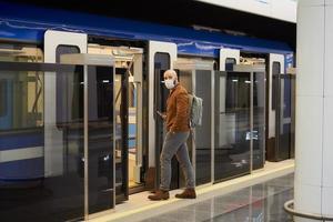 um homem com uma máscara facial de médico segurando um smartphone enquanto entra em um vagão do metrô foto