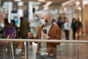 homem com máscara facial está usando um telefone e segurando um café no shopping foto
