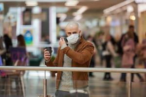 um homem está colocando uma máscara enquanto segura uma xícara de café no shopping foto