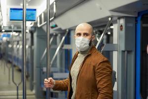 um homem careca com uma barba e uma máscara facial está segurando o corrimão em um vagão do metrô foto