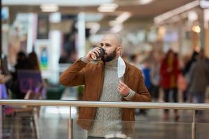 um homem está segurando uma máscara decolada enquanto bebe café no shopping foto