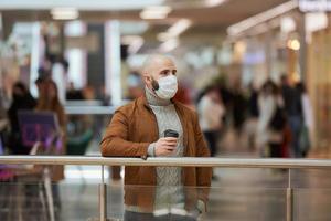 um homem com uma máscara facial está segurando uma xícara de café no shopping foto