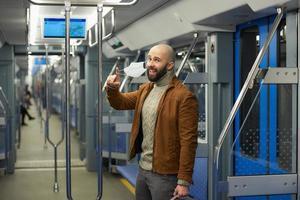 um homem com barba está tirando uma máscara médica e sorrindo em um trem foto