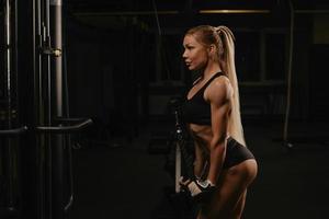 uma mulher em forma com longos cabelos loiros está fazendo uma flexão de corda de tríceps em uma academia foto