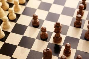 peças de xadrez em um tabuleiro de madeira. vista superior angular do xadrez.