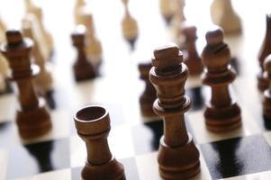 peças de xadrez em um tabuleiro de madeira. vista de peças de xadrez sob a luz do sol.
