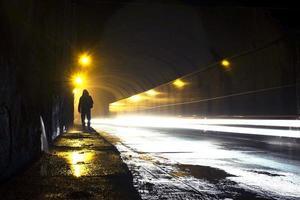 velho túnel úmido com a silhueta de um homem e trilhas de luz brilhante. foto
