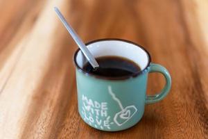 xícara de café preto fresco na mesa de madeira foto