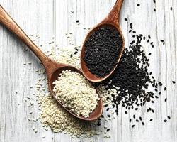 sementes de gergelim preto e branco em uma colher foto