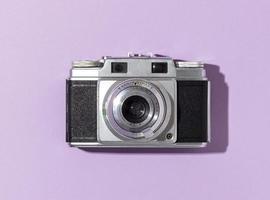 câmera vintage em fundo roxo foto