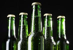 garrafas de cerveja verdes em fundo preto foto