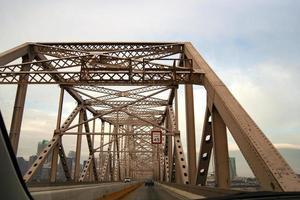 carros passando em uma velha ponte de metal foto