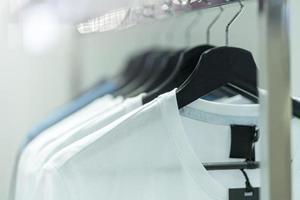 close-up de camisetas brancas em cabides, fundo de vestuário foto