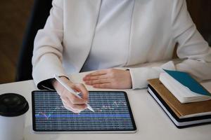 mulher revisando gráficos em um tablet foto