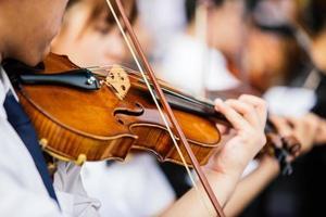 feche as mãos do violinista, estudante violinista tocando violino em concerto de orquestra foto