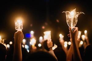 pessoas com as mãos segurando velas para orar foto