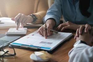 jovem contador, consultoria de equipe de marketing e usando uma calculadora para analisar o crescimento das vendas no mercado global de trabalho. conceito de contabilidade foto