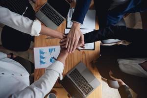 Feche a vista superior da parceria de negócios, juntando as mãos. trabalho em equipe e conceito de unidade. foto