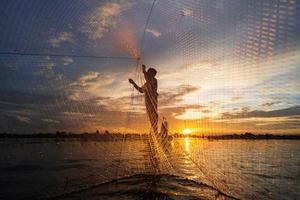silhueta de pescador em barco de pesca com rede no lago ao pôr do sol, Tailândia foto