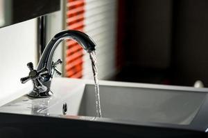 torneira e fluxo de água no banheiro foto