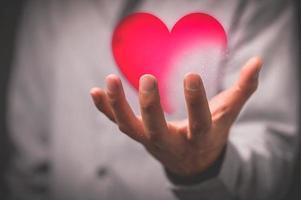 mão mostrando holograma do símbolo do coração foto