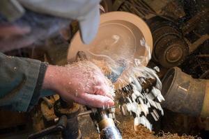 fazendo uma tigela de madeira em um torno em uma velha pequena oficina foto