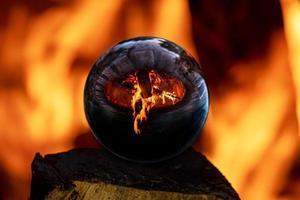 fogueira em uma lareira de pedra refletida em uma bola de vidro foto