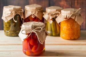 potes de vegetais fermentados em fundo de madeira foto