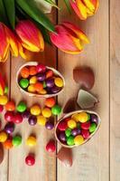 tulipas multicoloridas e ovos de páscoa de chocolate em um fundo de madeira foto