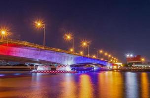 ponte lindamente iluminada sobre o rio à noite e um reflexo de água foto
