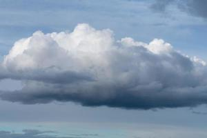 grande nuvem branca e cinza fofa no céu foto