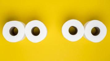 vista de cima rolos de papel higiênico em fundo amarelo foto