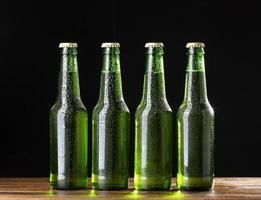 quatro garrafas de cerveja verdes em fundo preto foto