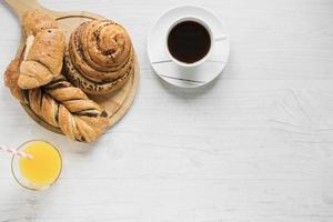 suco e café perto de pães com espaço de cópia foto