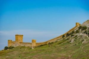 Fortaleza Genoese no topo da montanha contra o céu azul. foto