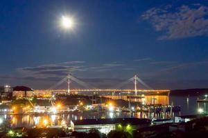 paisagem noturna com vista para a baía de diomida e a ponte russa. foto