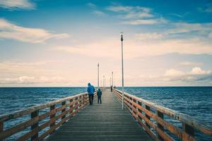 vista do mar com vista para o longo cais da cidade turística com pessoas caminhando. foto