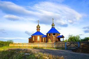 capela de madeira com telhado azul na costa da baía de cola. foto