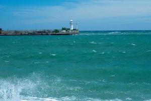 vista do mar com um farol branco no horizonte. foto
