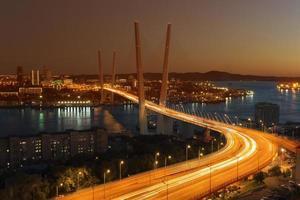 pôr do sol sobre vladivostok e vista da ponte dourada foto