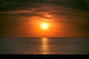 vista do mar com um belo pôr do sol sobre a água. foto