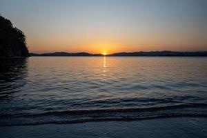 vista do mar com vista para a praia e o pôr do sol. foto