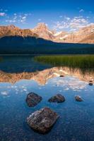 pico howse refletido no lago de aves aquáticas no parque nacional de banff, alberta, canadá ao nascer do sol foto